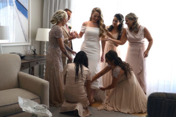 Bride is being helped by bridessmades